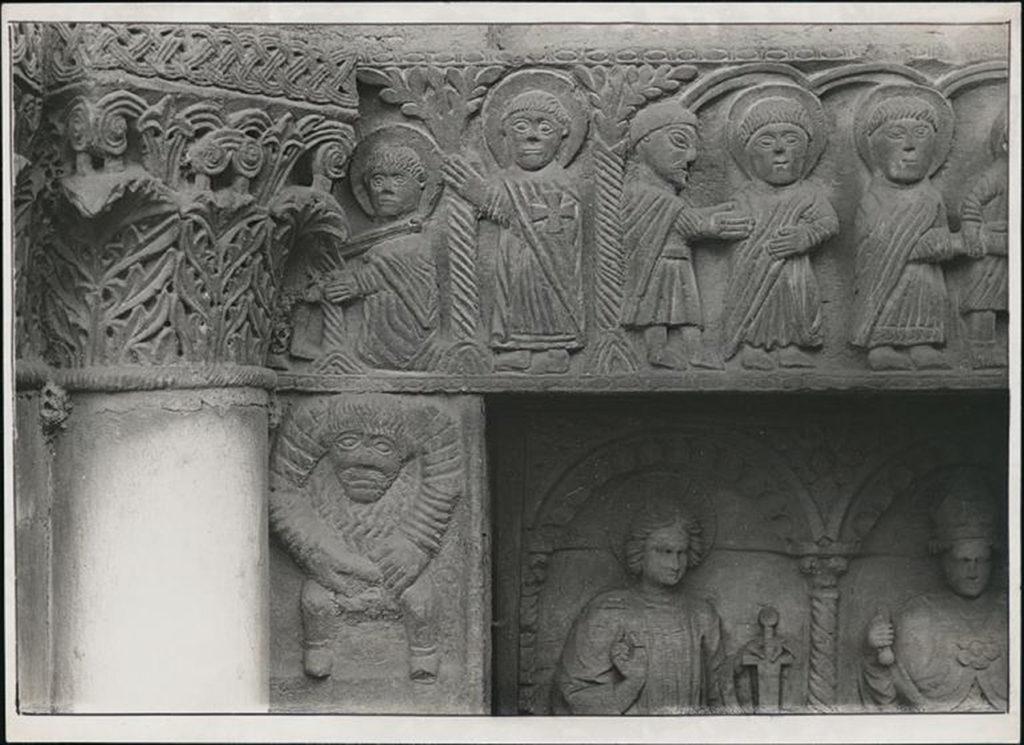 Portale maggiore della chiesa di S. Celso. Particolare del lato sinistro della trabeazione scolpita a rilievo con scene della vita di S. Nazaro e S. Celso; è inoltre visibile il capitello e parte delle formelle in legno intagliato della porta