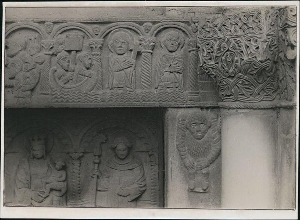 Portale maggiore della chiesa di S. Celso. Particolare del lato destro della trabeazione scolpita a rilievo con scene della vita di S. Nazaro e S. Celso; è inoltre visibile il capitello e parte delle formelle in legno intagliato della porta
